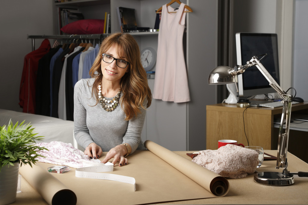 Portrait of creative businesswoman standing at her designer studio in front of desk an working. Professional female looking at camera and smiling. Small business.